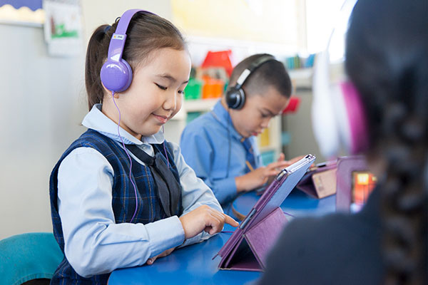 Students using tablets in modern classroom at St Agnes Catholic Primary School Matraville