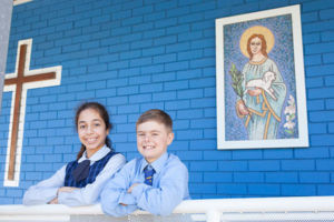 Students at St Agnes Catholic Primary School Matraville smiling in front of mosaic of St Agnes