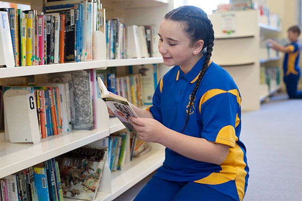 St Agnes Catholic Primary School Matraville student selecting book in school library