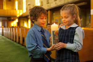 Students of St Agnes Catholic Primary School Matraville in church holding school candle